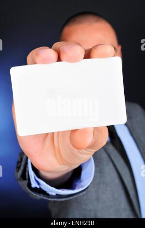 Un jeune homme de race blanche portant un costume gris détient une pancarte blanche dans sa main Banque D'Images