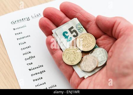 Une femme pauvre retraité senior une petite quantité d'argent comptant libre de faible valeur dans la main avec une liste de courses pour l'épicerie. England UK