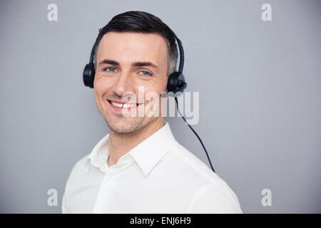 Jeune homme au casque de l'opérateur à la caméra à l'arrière-plan gris plus