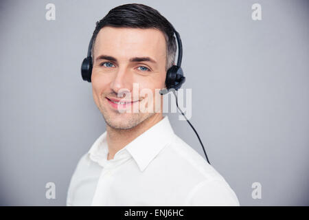 Happy young woman in headphones sur fond gris. Looking at camera