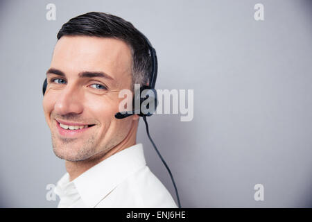 Cheerful businessman in headphones debout sur gray backgorund et looking at camera