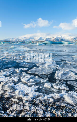 Montagnes derrière l'eau congelée de Iceberg Jökulsárlón Jökulsárlón, lagon, au sud est de l'Islande, les régions Banque D'Images