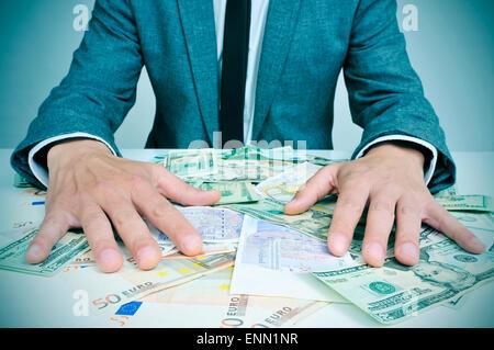 Closeup of a young man in suit assis à son bureau 24 plein d'euro et dollar bills d'essayer de les retenir, représentant Banque D'Images