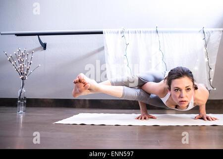 Femme forte détient l'équilibre du bras de yoga Banque D'Images