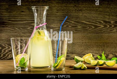 Limonade rafraîchissante boisson et fruits mûrs contre fond de bois Banque D'Images