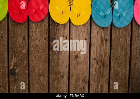 Tongs multicolores sur terrasse en bois Banque D'Images