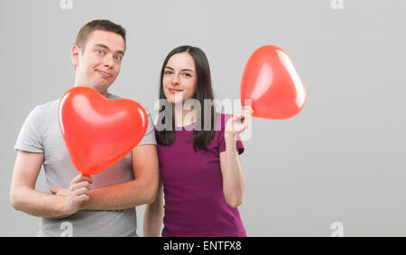 Loving young couple holding heart shaped balloons et souriant. copie espace disponible Banque D'Images