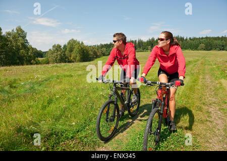 Jeune couple équitation vtt au printemps meadow