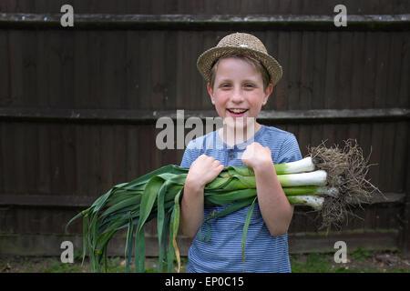 Un garçon heureux avec des poireaux biologiques cultivés cueillis dans le jardin Banque D'Images