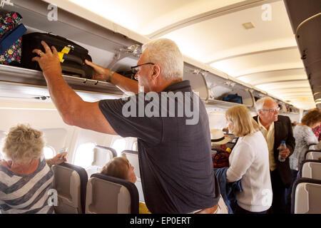 Passager d'un avion le stockage de bagage à main dans le compartiment au-dessus sur un Monarch Airlines vol de Madère à l'aéroport de Gatwick, UK
