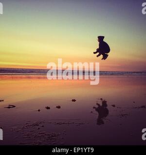 Garçon sautant sur la plage Banque D'Images