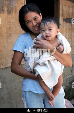 Mère tenant son fils (10 mois) après un bain dans une baignoire dans une serviette. Township Paranaque, Manille, Banque D'Images