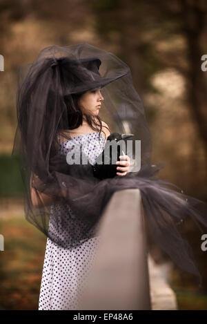 Fille dans un voile noir tenant un oiseau noir farci Banque D'Images