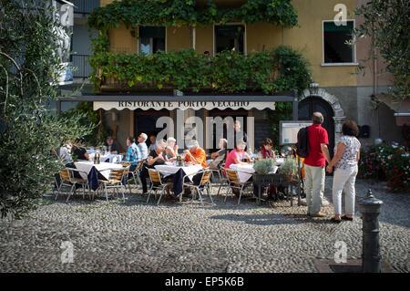 Les personnes bénéficiant de manger dehors à l'extérieur d'un petit restaurant à Malcesine, sur le lac de Garde, Banque D'Images