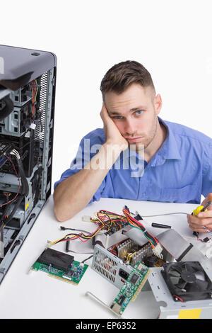 Portrait of young fatigué ingénieur en informatique avec des pièces de l'unité centrale Banque D'Images