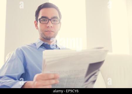 Fronçant man looking at camera et tenant un journal