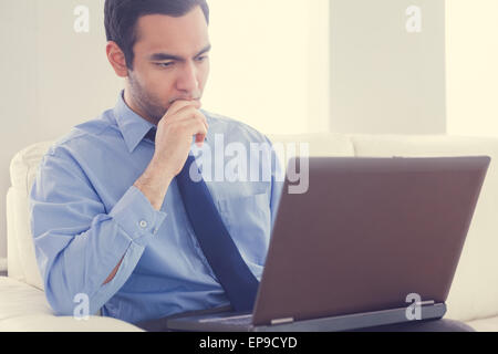 L'homme a souligné à l'aide d'un laptop sitting on a sofa