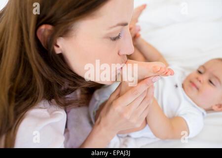 Mère embrassant son lit sur la jambe de babys Banque D'Images
