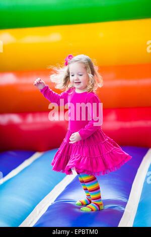 Funny cute little girl préscolaire jouer, sauter et rebondir dans un château gonflable à l'anniversaire d'une aire Banque D'Images