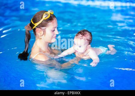 Adorable baby girl enjoying nager dans une piscine avec sa mère, au développement du class pour les nourrissons Banque D'Images