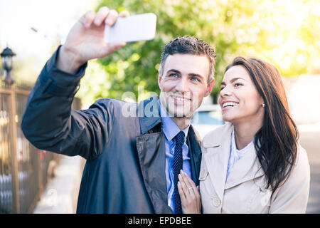 Laughing woman et homme heureux faire photo sur smartphone outdoors selfies Banque D'Images