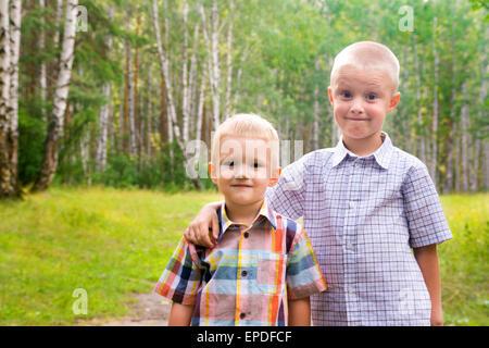 Deux beaux enfants blonds smiling happy joyeux (petits garçons, frères) à l'extérieur et s'amuser dans le parc d'été. Banque D'Images