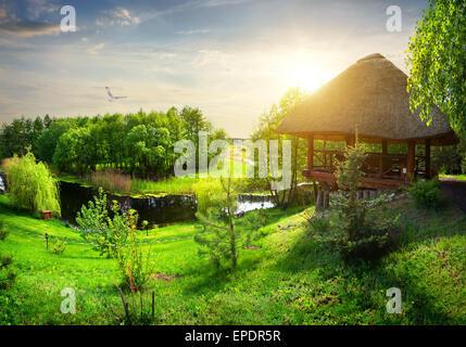 Tonnelle en bois avec toit de chaume près de la rivière Banque D'Images