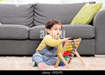Jolie petite fille assise sur le plancher à la maison et jouer avec un boulier Banque D'Images