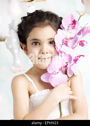 Petite fille brune tenant une fleur colorée Banque D'Images