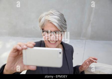 Portrait of smiling femme de carrière en tenant un smartphone avec selfies Banque D'Images