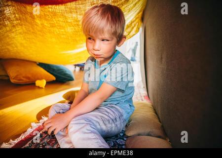 Portrait de petit garçon assis dans une couverture cave faisant un drôle de visage Banque D'Images
