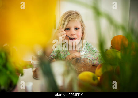 Blonde girl eating at table Banque D'Images