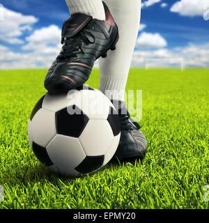 76a40346e1 Joueur de football dans les pieds posent sur un simple terrain de jeu, avec  sky