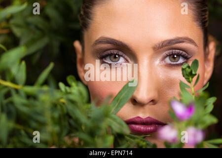 Belle jeune femme posant parmi les feuilles vertes