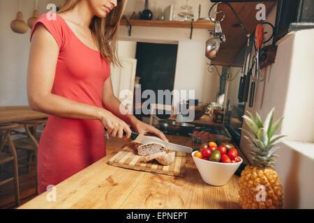 Cropped shot of a young woman slicing une miche de pain frais cuit sur un comptoir de cuisine domestique. Le petit Banque D'Images