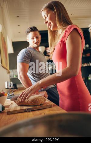 Coup de jeune couple debout dans la cuisine. Jeune femme avec du pain coupe homme debout par. L'accent sur femme Banque D'Images