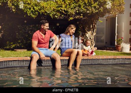 Couple assis sur le bord de la piscine avec leurs enfants profiter d'une chaude journée d'été près de la piscine. Banque D'Images