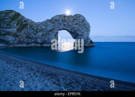 Durdle door dans le clair de lune, Dorset, Angleterre. Capturé en fin de soirée que la lune à travers la roche inondées's Banque D'Images