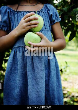 Une jeune fille tient la pomme verte dans un verger. Banque D'Images