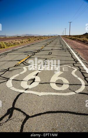 Emblème de la Route 66 peint sur la surface de la route sur le lonely étirement au désert de Californie USA Banque D'Images
