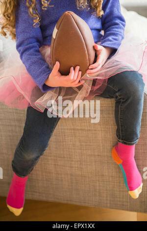 Girl (10-11) wearing tutu jouant avec football Banque D'Images