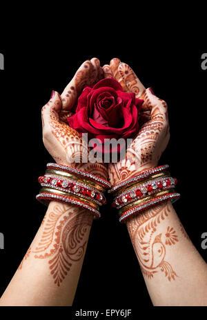 Les mains de henné holding femme rose rouge isolé sur fond noir avec le chemin de détourage Banque D'Images