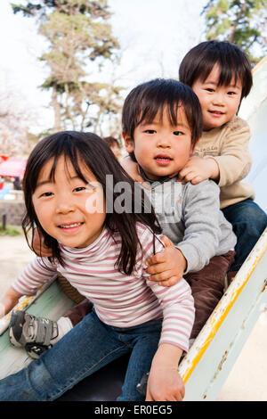 Trois jeunes enfants japonais, une fille, deux garçons, 4-5 ans, assis sur une glissade se tenant les uns contre Banque D'Images