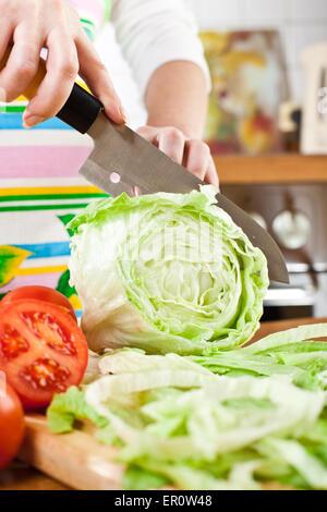 Woman's hands cutting laitue, derrière les légumes frais. Banque D'Images