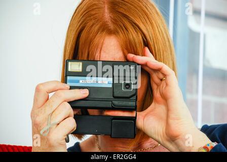 Redhaired femme utilise un appareil photo Kodak Disc qui étaient populaires dans les années 1980. Banque D'Images