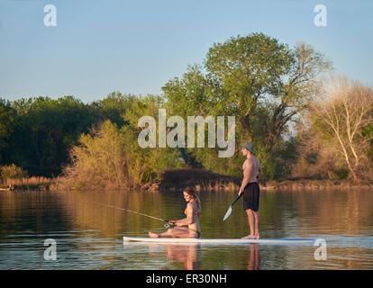Un jeune couple en maillot de pêche un paddle board sur un petit lac dans le Nord de la Californie. Banque D'Images