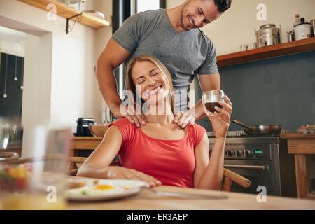 Happy young woman holding tablet petit déjeuner tasse de café d'obtenir un massage de l'épaule de son petit ami. Banque D'Images
