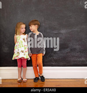 Little Boy and Girl standing in front of blackboard à l'un l'autre. Tourné à l'intérieur d'enfants à la maison avec l'exemplaire de l'espace.
