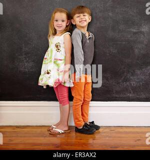 Little Boy and Girl standing in front of blackboard looking at camera de sourire. Longueur totale de l'image deux innocents li