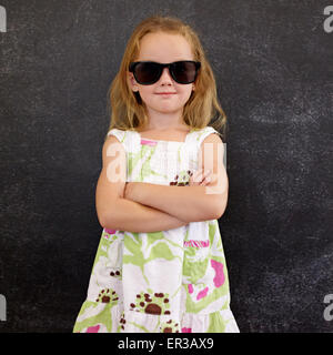 Portrait of cute little girl wearing sunglasses contre un mur noir. Jeune fille debout dans les tons avec ses mains pliées.